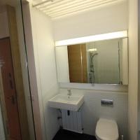 garzonlakás belsőépítészete, mosdó és wc a fürdőszobában